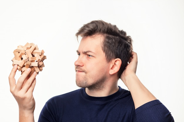 Uomo attraente di affari di 25 anni che sembra sconcertante il puzzle di legno.