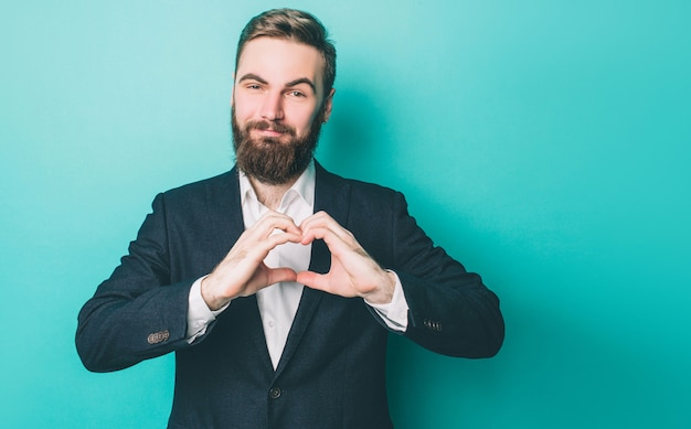 Uomo attraente e amato sta mostrando il segno del cuore con le mani e il sorriso.