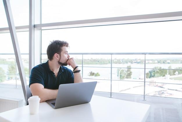 Uomo attraente in un caffè seduto con un caffè e un computer portatile, guarda fuori dalla finestra con un bellissimo paesaggio