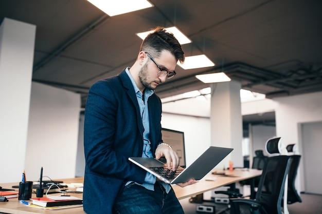 Uomo attraente serio in glassess è in piedi vicino al posto di lavoro in ufficio. indossa camicia blu, giacca scura. sta scrivendo sul laptop.