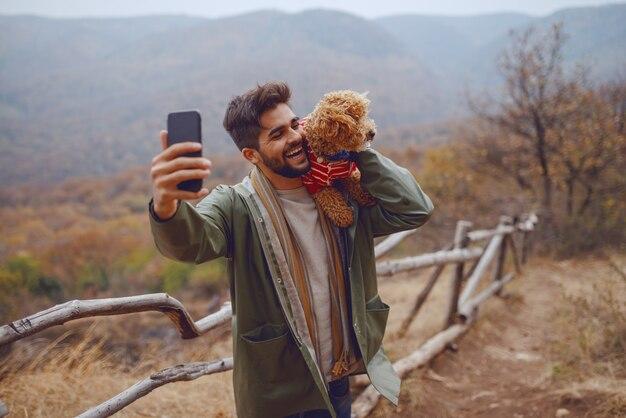 Uomo attraente sorridente della corsa in impermeabile che prende selfie con il suo cane. tempo d'autunno.