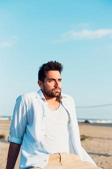 Uomo attraente sulla spiaggia che osserva via