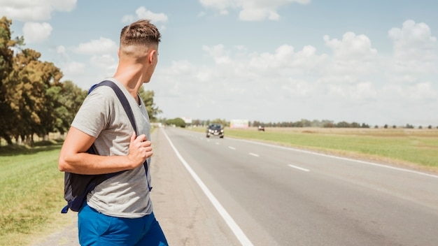 Uomo autostop su una strada