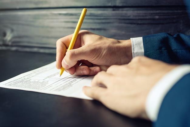Uomo avvocato o firma documenti ufficiali con una penna
