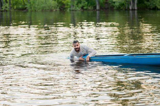 Uomo bagnato che tiene la canoa
