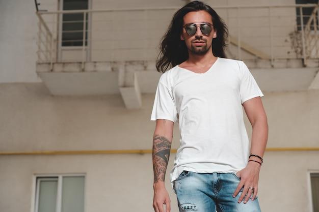 Uomo barbuto alla moda che posa gli occhiali da sole alla moda