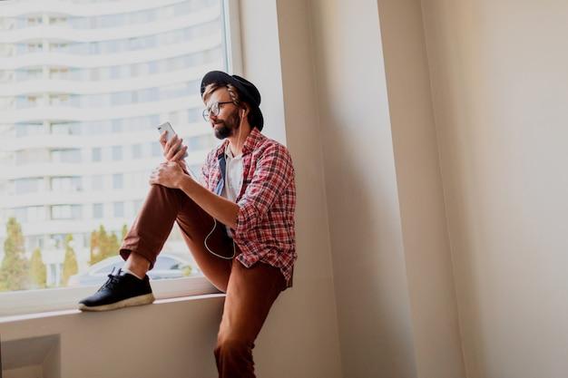 Uomo barbuto alla moda in camicia a scacchi luminosa che installa nuova applicazione mobile