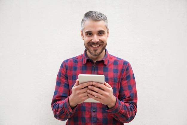 Uomo barbuto allegro con tablet pc