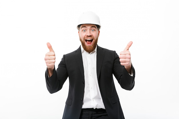 Uomo barbuto allegro di affari in casco protettivo che mostra i pollici su