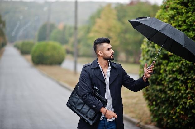 Uomo barbuto alto alla moda che indossa cappotto nero con custodia per ombrello e borsa posta al giorno di pioggia