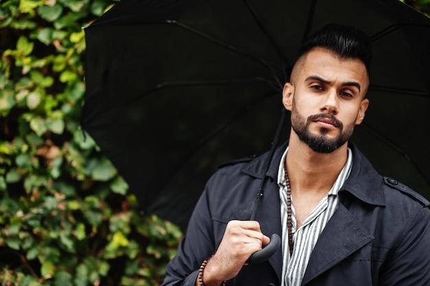Uomo barbuto alto alla moda che porta cappotto nero con l'ombrello posato al giorno del tempo di pioggia