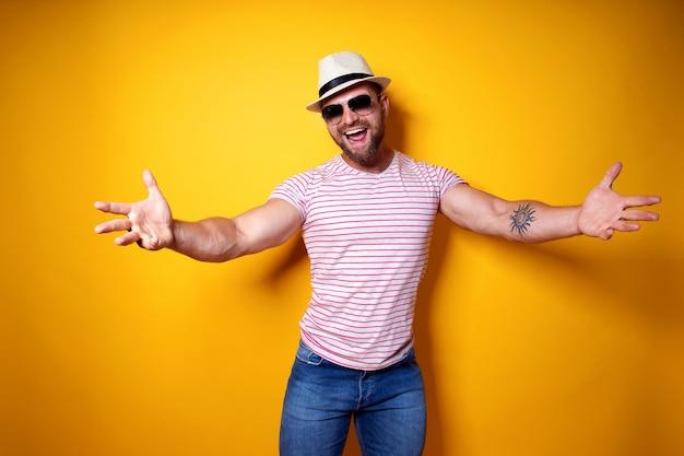 Uomo barbuto amichevole positivo in vestito e cappello spogliati d'avanguardia che tirano le mani verso