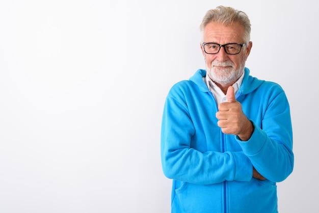 Uomo barbuto anziano bello che dà pollice in su pronto per la palestra su bianco
