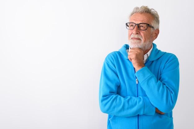 Uomo barbuto anziano bello pensare mentre cerca pronto per la palestra su bianco