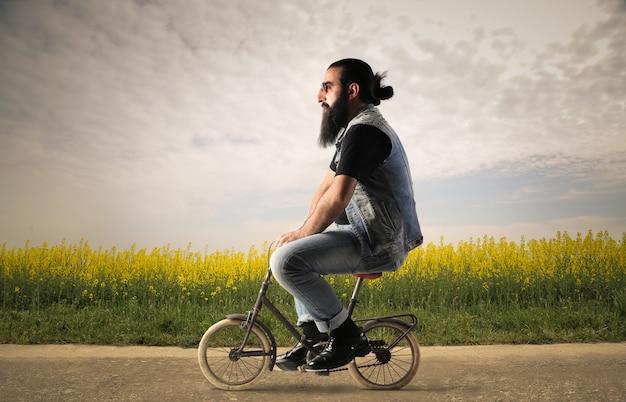 Uomo barbuto arabo in sella a una piccola bicicletta