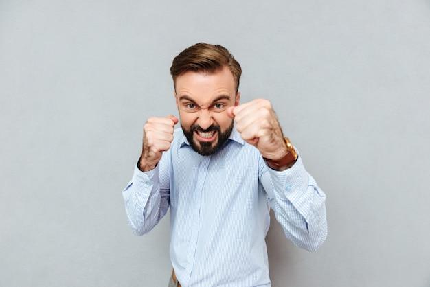 Uomo barbuto arrabbiato in vestiti di affari pronti a combattere