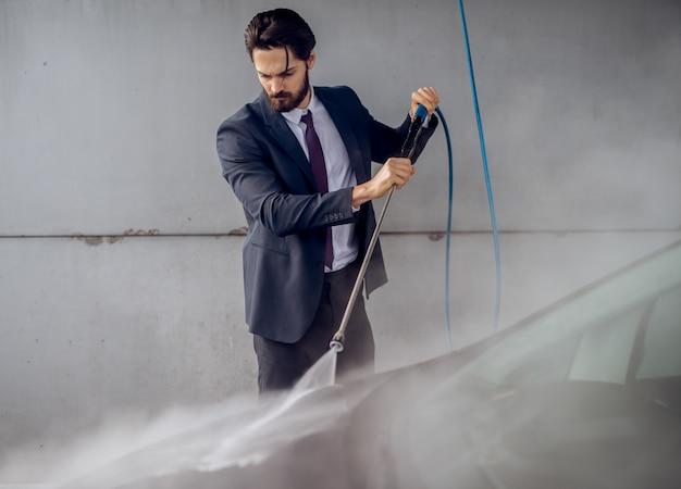 Uomo barbuto attraente concentrato serio in vestito che lava la sua automobile alla stazione di self service di lavaggio manuale dell'automobile.