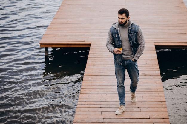 Uomo barbuto bello che beve caffè dal fiume in parco