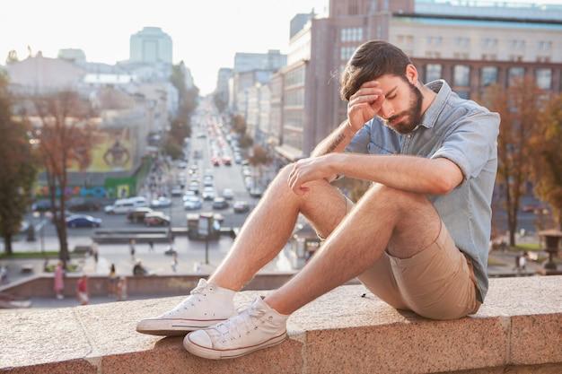 Uomo barbuto bello che gode del giorno caldo alla città