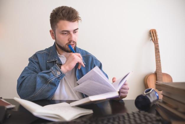 Uomo barbuto bello che si siede ai libri di lettura della tavola l'uomo è impegnato nell'autoistruzione a casa.