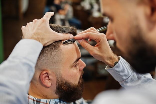 Uomo barbuto bello dal barbiere, barbiere al lavoro.