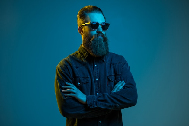 Uomo barbuto bello dei pantaloni a vita bassa che indossa gli occhiali da sole rotondi isolati sopra spazio leggero blu