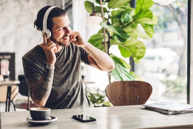 Uomo barbuto bello dei pantaloni a vita bassa che si rilassa ascoltando la musica con le cuffie e caffè alla tavola in caffè concetto di tecnologia e di comunicazione