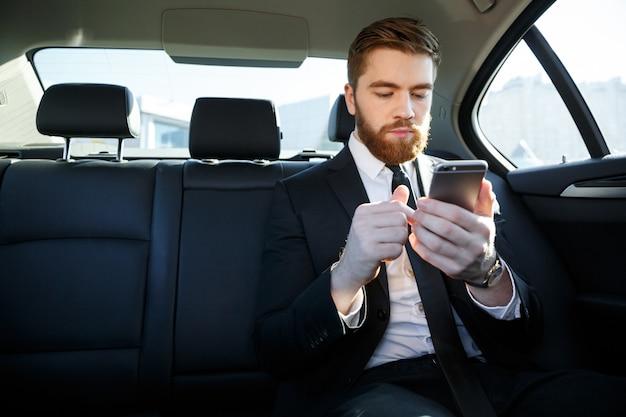 Uomo barbuto bello di affari in vestito facendo uso del telefono cellulare