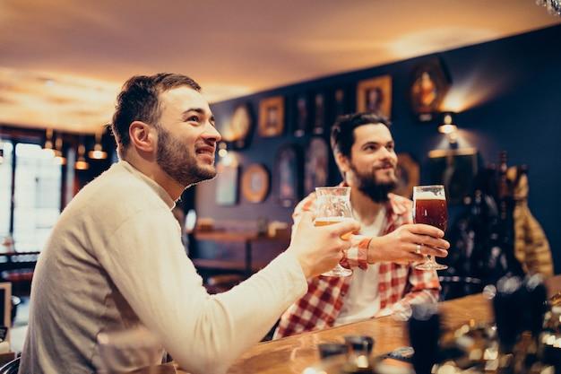 Uomo barbuto bello due che beve birra in pub