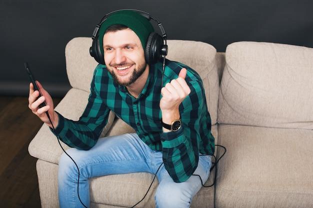 Uomo barbuto bello giovane hipster seduto su un divano a casa, ascoltando musica in cuffia