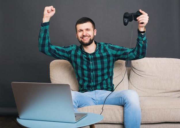 Uomo barbuto bello giovane hipster seduto sul divano a casa, giocando a videogiochi su notebook, tenendo il joystick, camicia a scacchi verde, felice, sorridente, divertimento, intrattenimento, celebrando la vittoria, mani in alto
