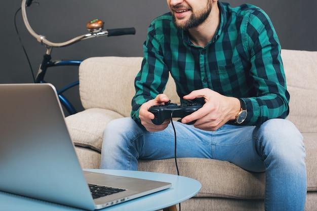 Uomo barbuto bello giovane hipster seduto sul divano a casa, giocare a videogiochi su notebook