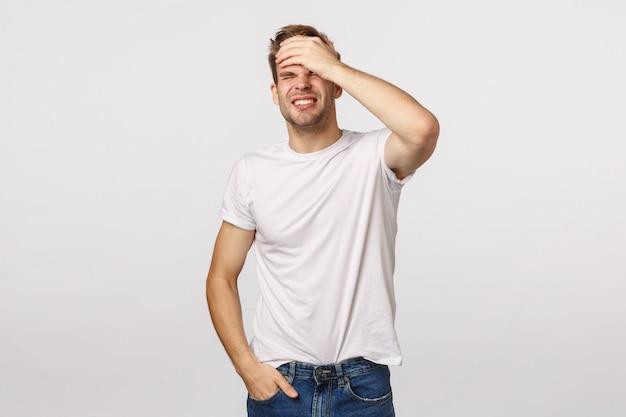 Uomo barbuto biondo attraente in fronte bianca di perforazione della maglietta