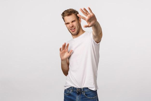 Uomo barbuto biondo attraente in maglietta bianca che si difende