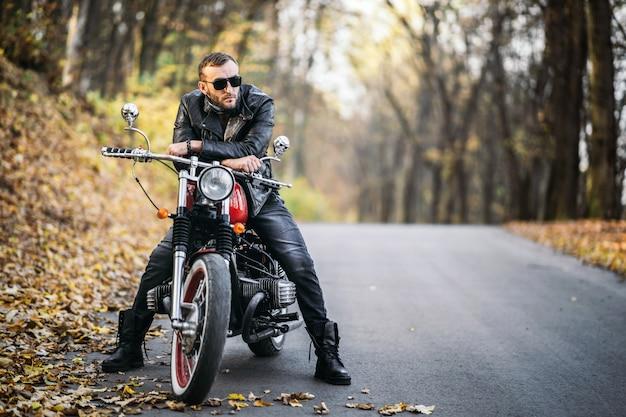 Uomo barbuto brutale in occhiali da sole e giacca di pelle seduto su una moto sulla strada nella foresta
