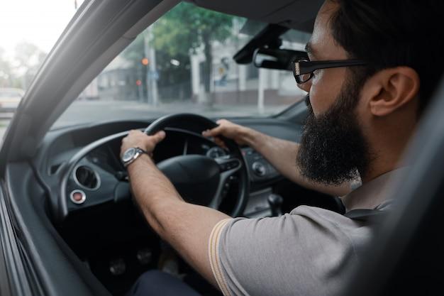 Uomo barbuto casual moderno alla guida di un'auto