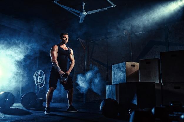 Uomo barbuto caucasico attraente muscolare che solleva due kettlebell in una palestra. piatti, manubri e pneumatici in background.