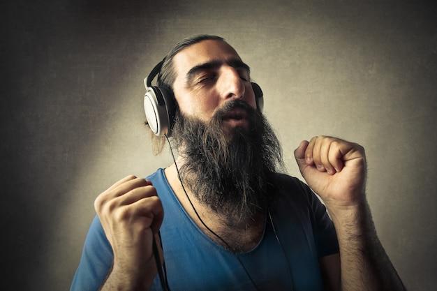 Uomo barbuto che ascolta la musica