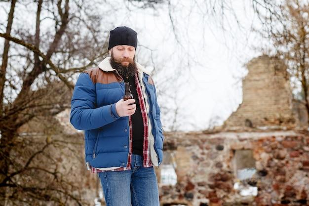 Uomo barbuto che beve birra in inverno nella foresta