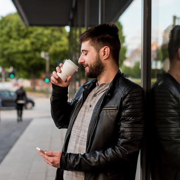 Uomo barbuto che beve dalla tazza e usando smartphone