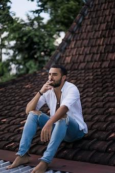 Uomo barbuto che fuma sul tetto