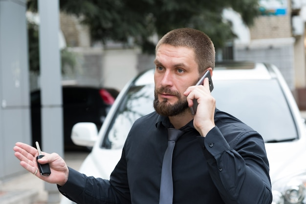 Uomo barbuto che parla emotivamente al telefono vicino all'automobile