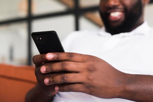 Uomo barbuto che passa in rassegna il suo telefono cellulare