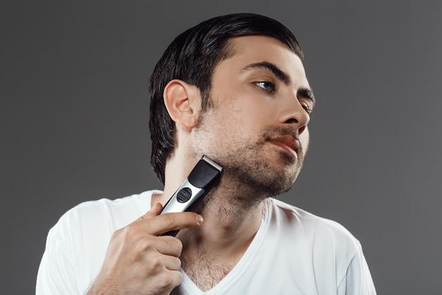 Uomo barbuto che rade barba, preparandosi
