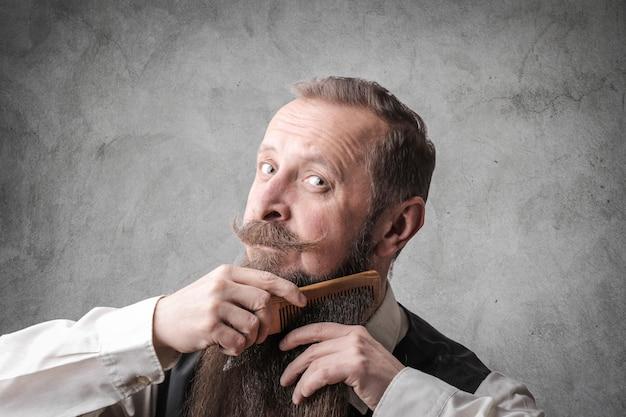 Uomo barbuto che si pettina la barba