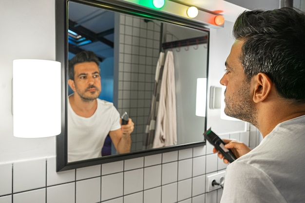 Uomo barbuto che si rade il viso