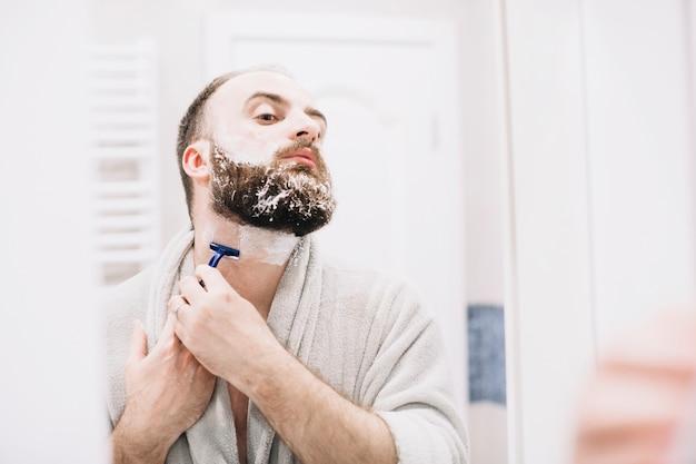 Uomo barbuto che si rade in accappatoio