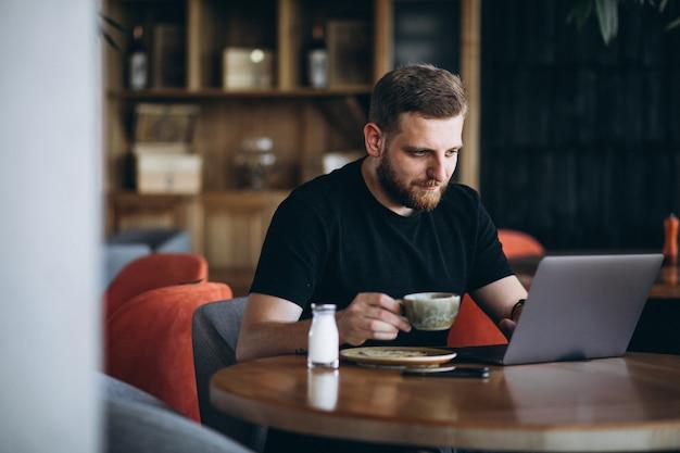 Uomo barbuto che si siede in un caffè bevendo caffè e lavorando su un computer