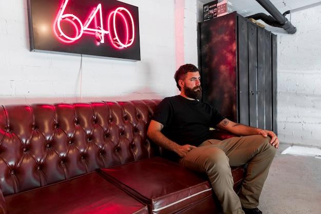 Uomo barbuto che si siede sul divano nel salone di barbiere