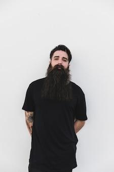 Uomo barbuto che sta contro il contesto bianco